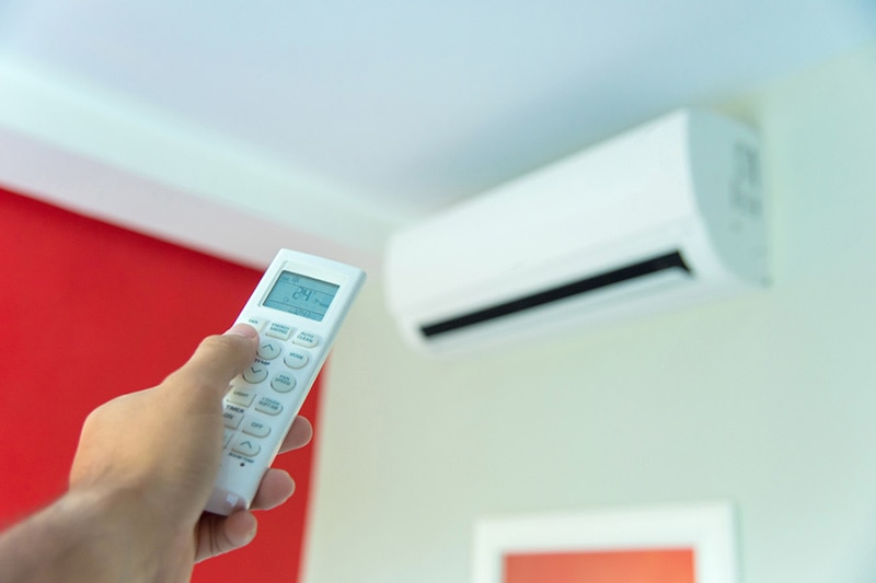 hand holding remote to ductless ac unit
