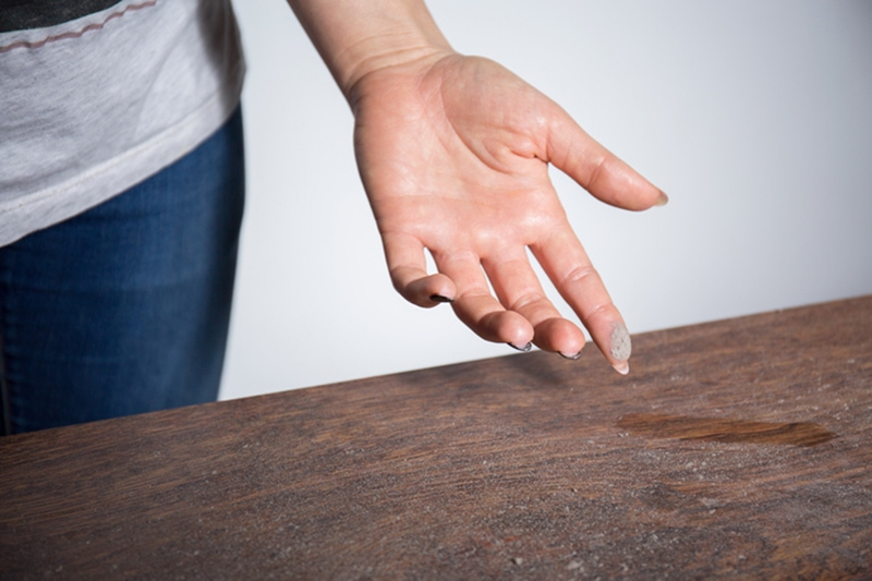 A hand that has just wiped some dust off a table | How To Eliminate Dust In My Home | Lake Charles, LA
