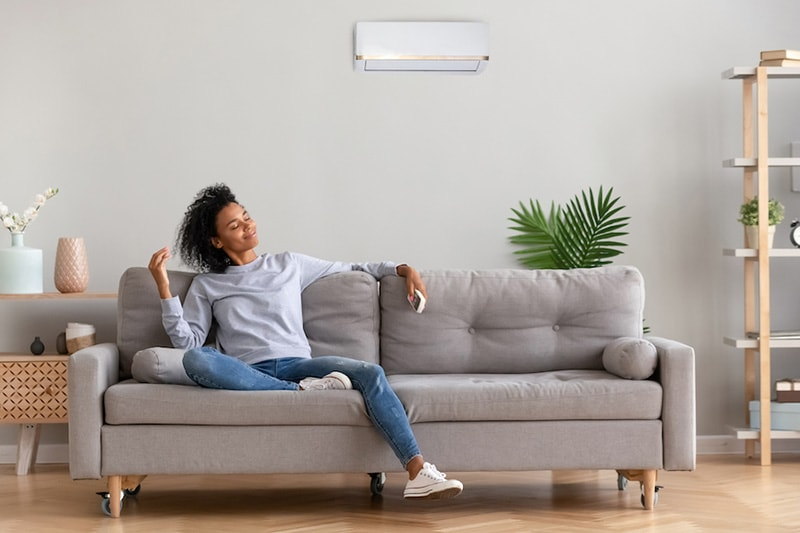 Woman on couch in jeans smelling fresh indoor air