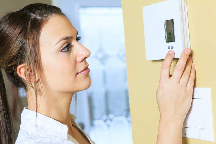 young-woman-adjusting-thermostat